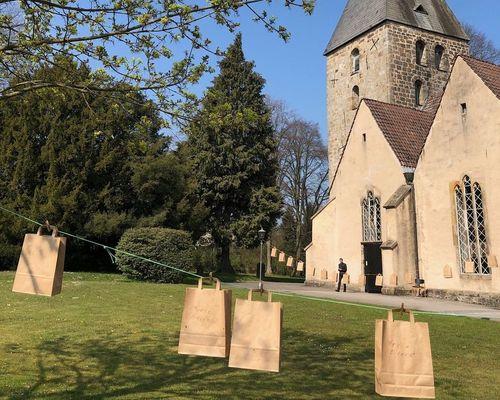 Papiertaschen mit einem Gottesdienst to go Ostern 2020 auf zwei Wäscheleinen vor der Kirche